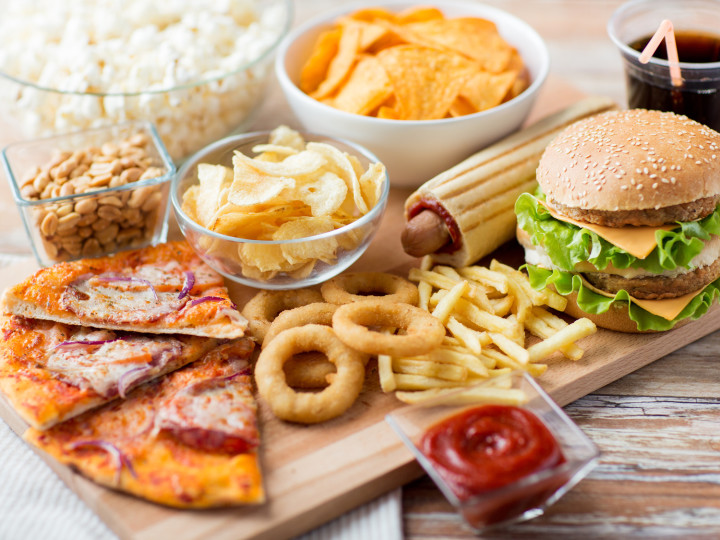 fast food and unhealthy eating concept - close up of fast food snacks and coca cola drink on wooden table